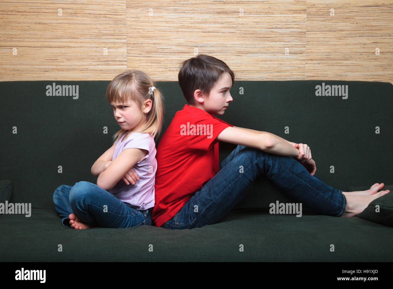 Brother and sister  wearing casual clothes  sitting on a green sofa back to back sad and frown - Stock Image