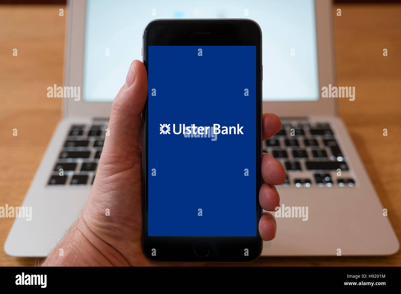 Using iPhone smart phone to display website logo of Ulster Bank - Stock Image