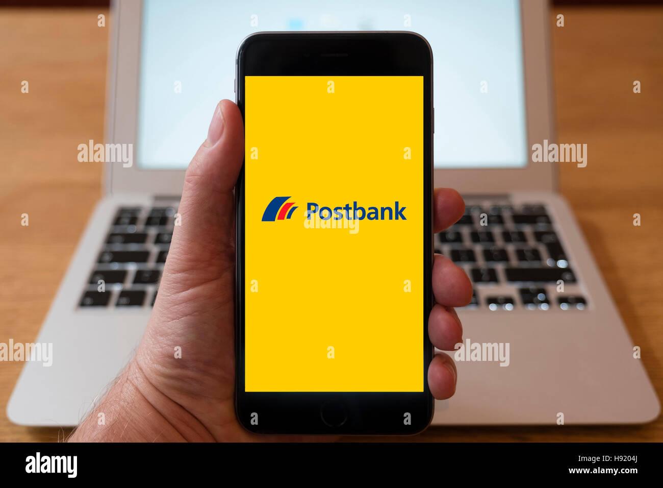 Using iPhone smart phone to display website logo of Postbank, German retail bank - Stock Image