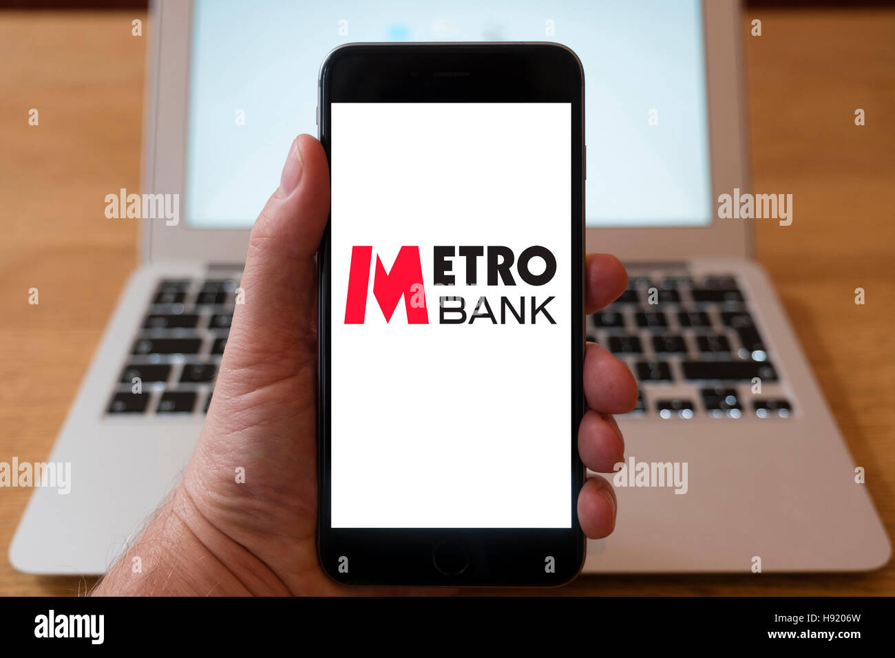 Using iPhone smart phone to display website logo of Metro Bank UK retail Bank - Stock Image