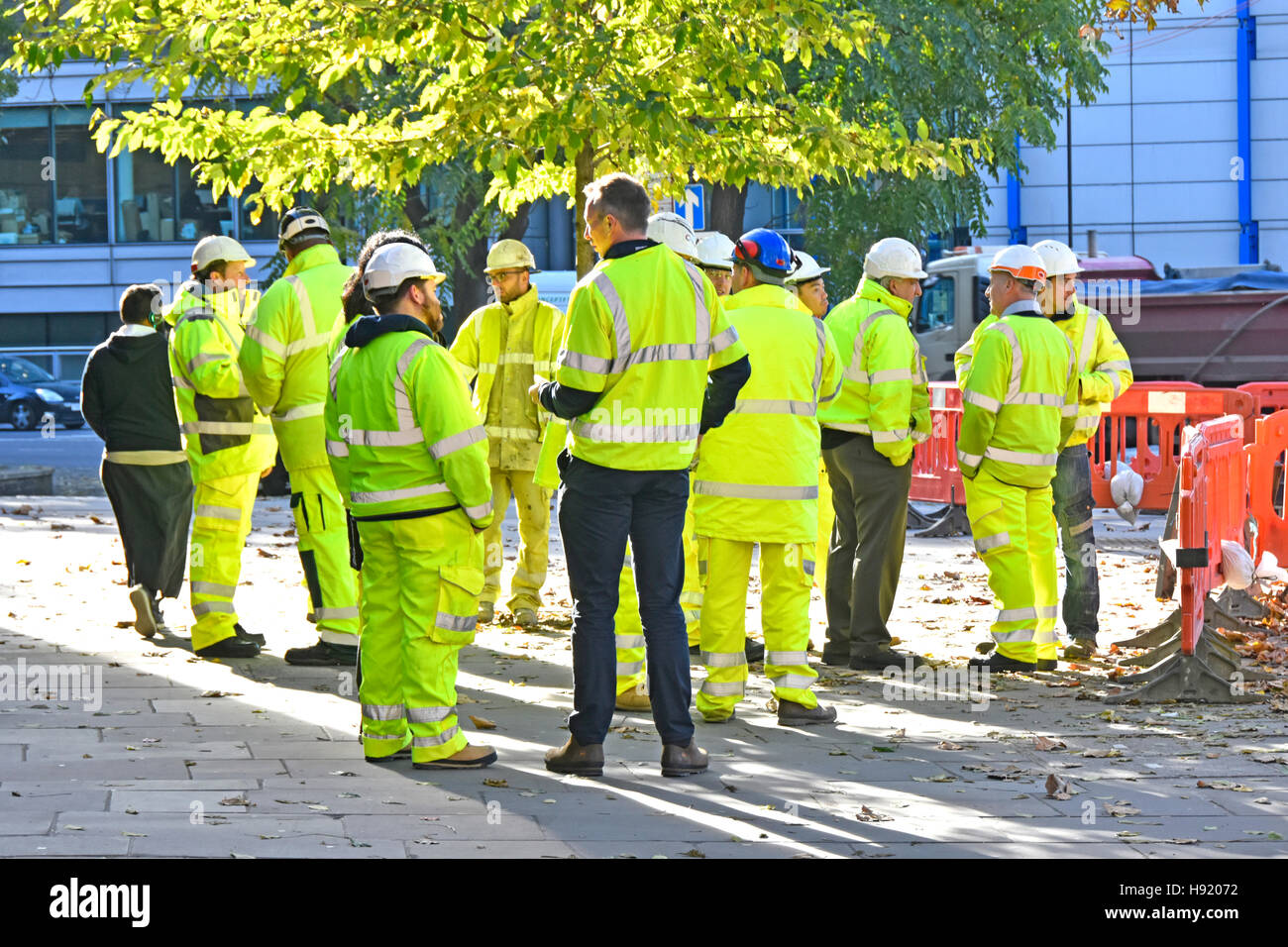 Group managers supervisors engineers foremen surveyors meeting adjacent to major road works project company logos - Stock Image