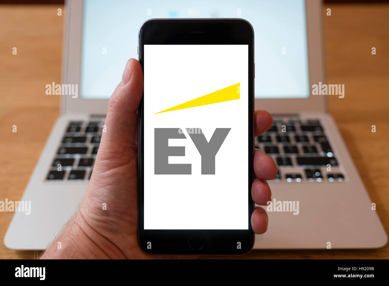 Using iPhone smart phone to display website logo of EY (Ernst & Young) a multinational professional services - Stock Image