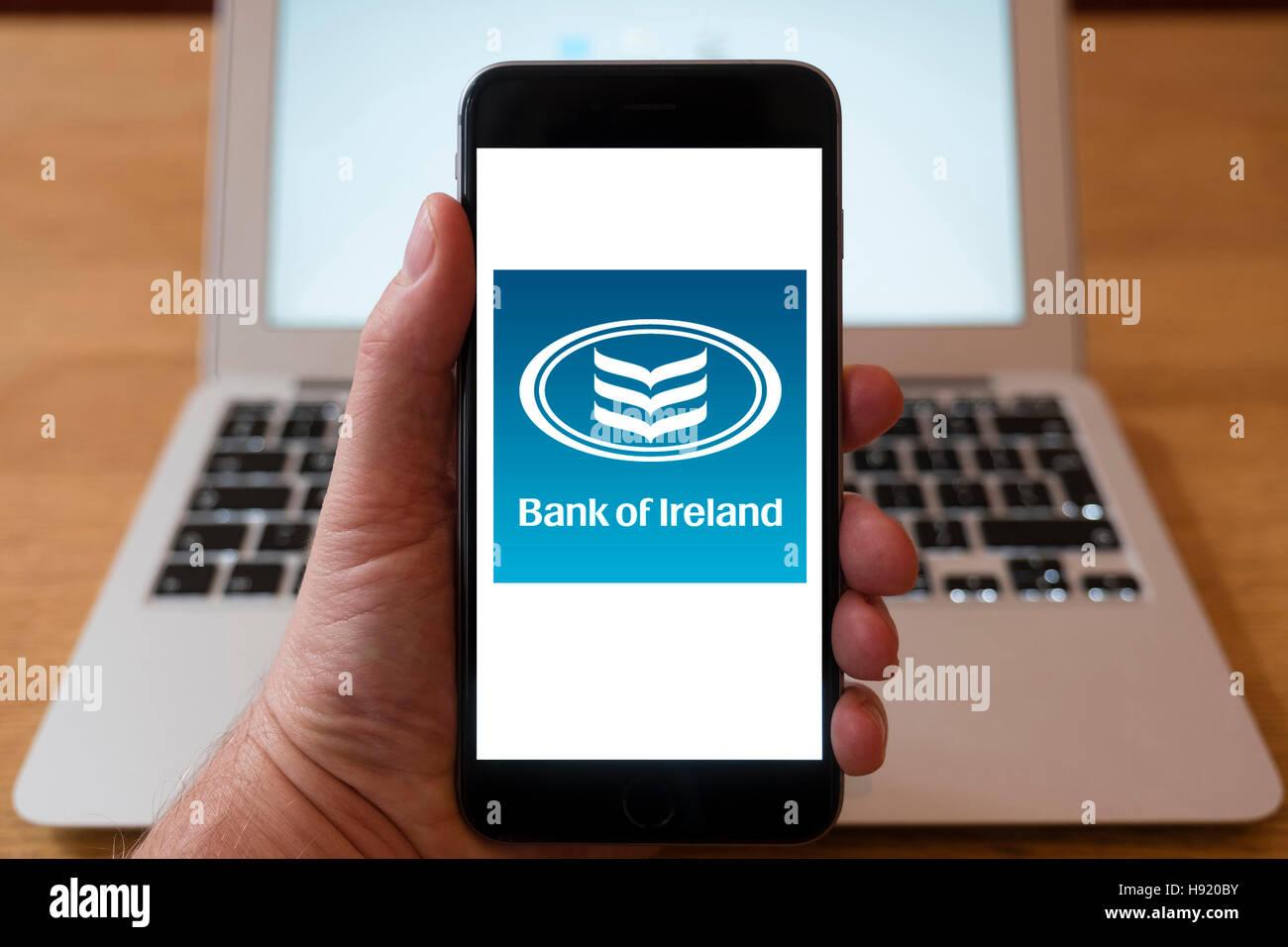 Using iPhone smart phone to display website logo of Bank of Ireland - Stock Image