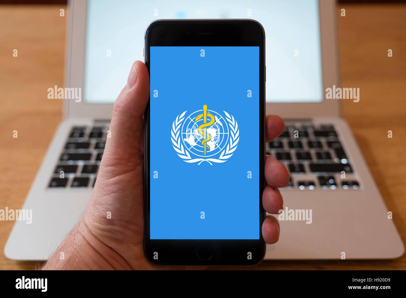 Using iPhone smart phone to display website logo of World Health Organisation - Stock Image