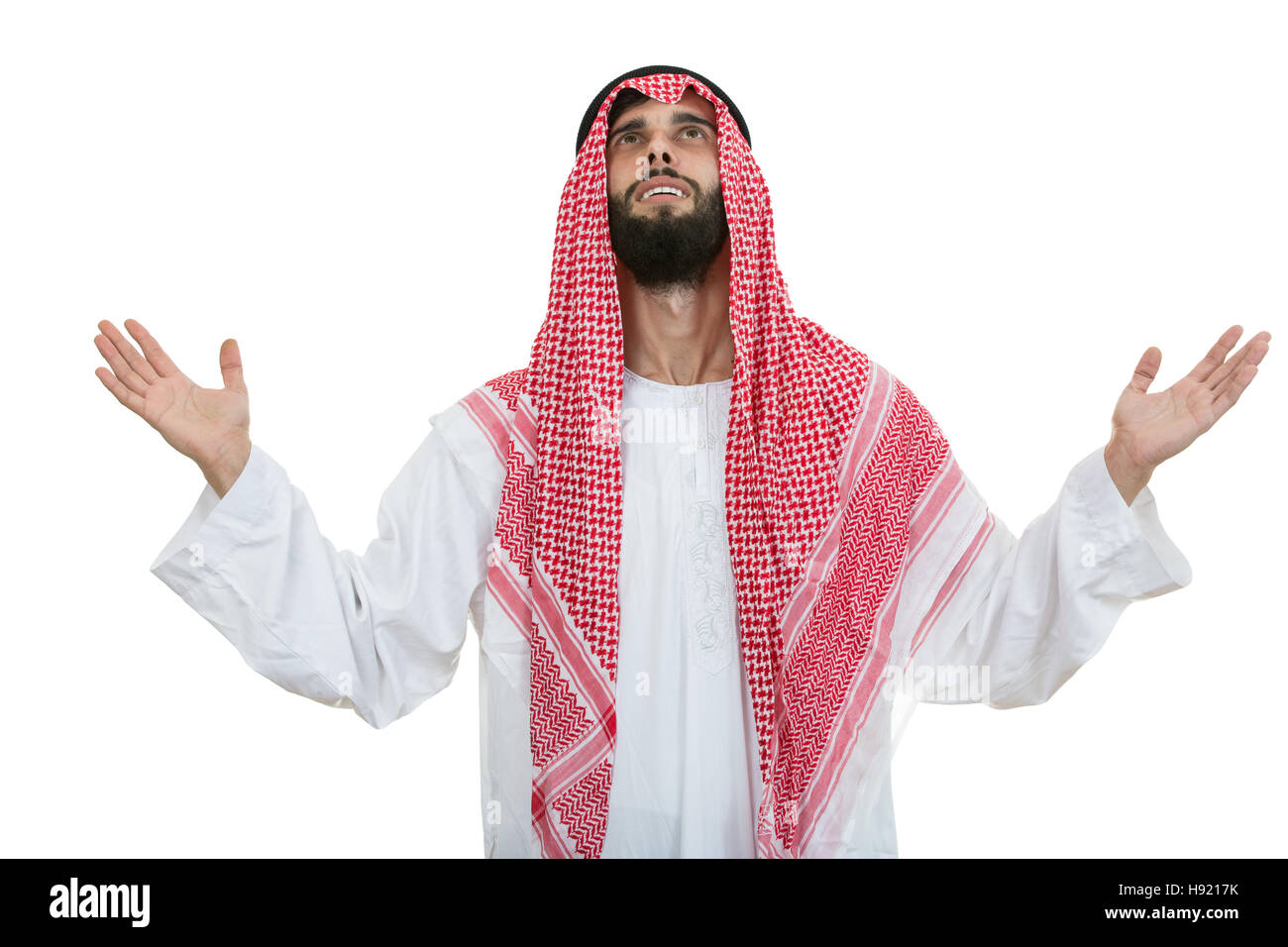 Young arab man of muslim religion praying isolated on white background - Stock Image