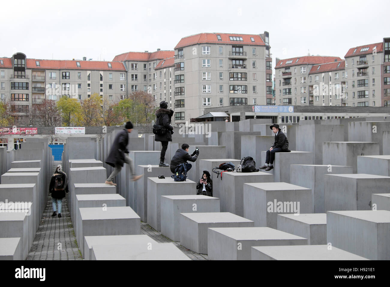Tourists standing photographing on the Memorial to the Murdered Jews of Europe in Berlin, Germany, Europe, EU   - Stock Image