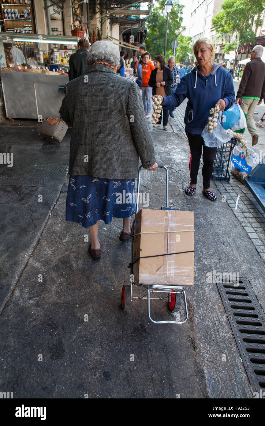 A street vendor offers garlic for sale to an old lady in central Athens - Stock Image