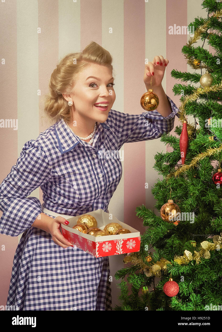 portrait of nice young woman hanging around christmas tree on x-mas  eve - Stock Image