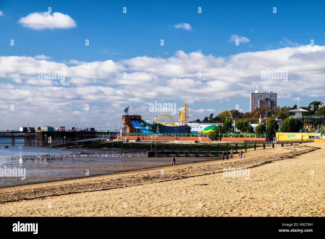 Pier and Adventure Island funfair and people walking on beach at low tide. Southend-on-sea, Essex,England - Stock Image