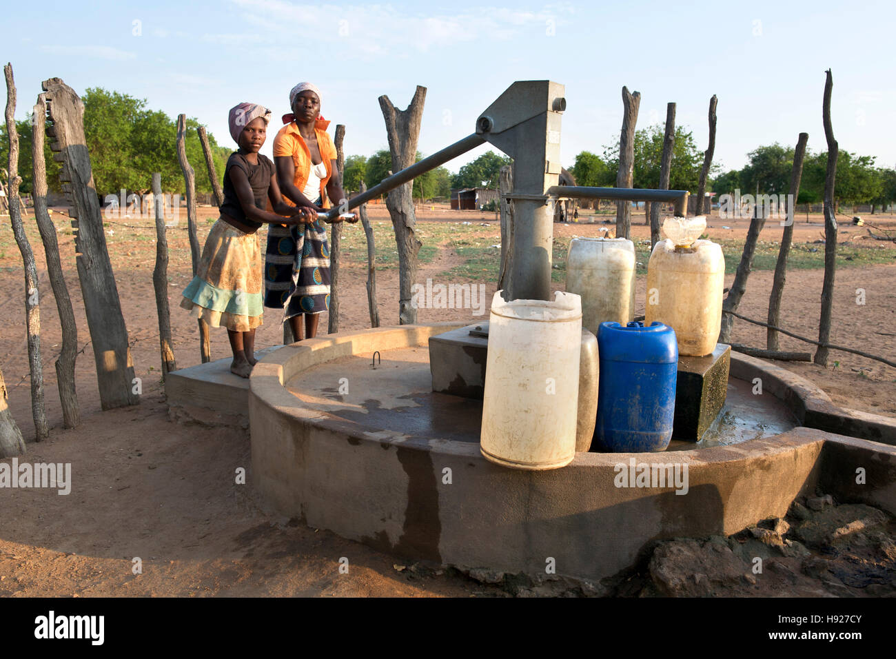 Two African women pumping water in the Mozambican town of Mpelane. - Stock Image