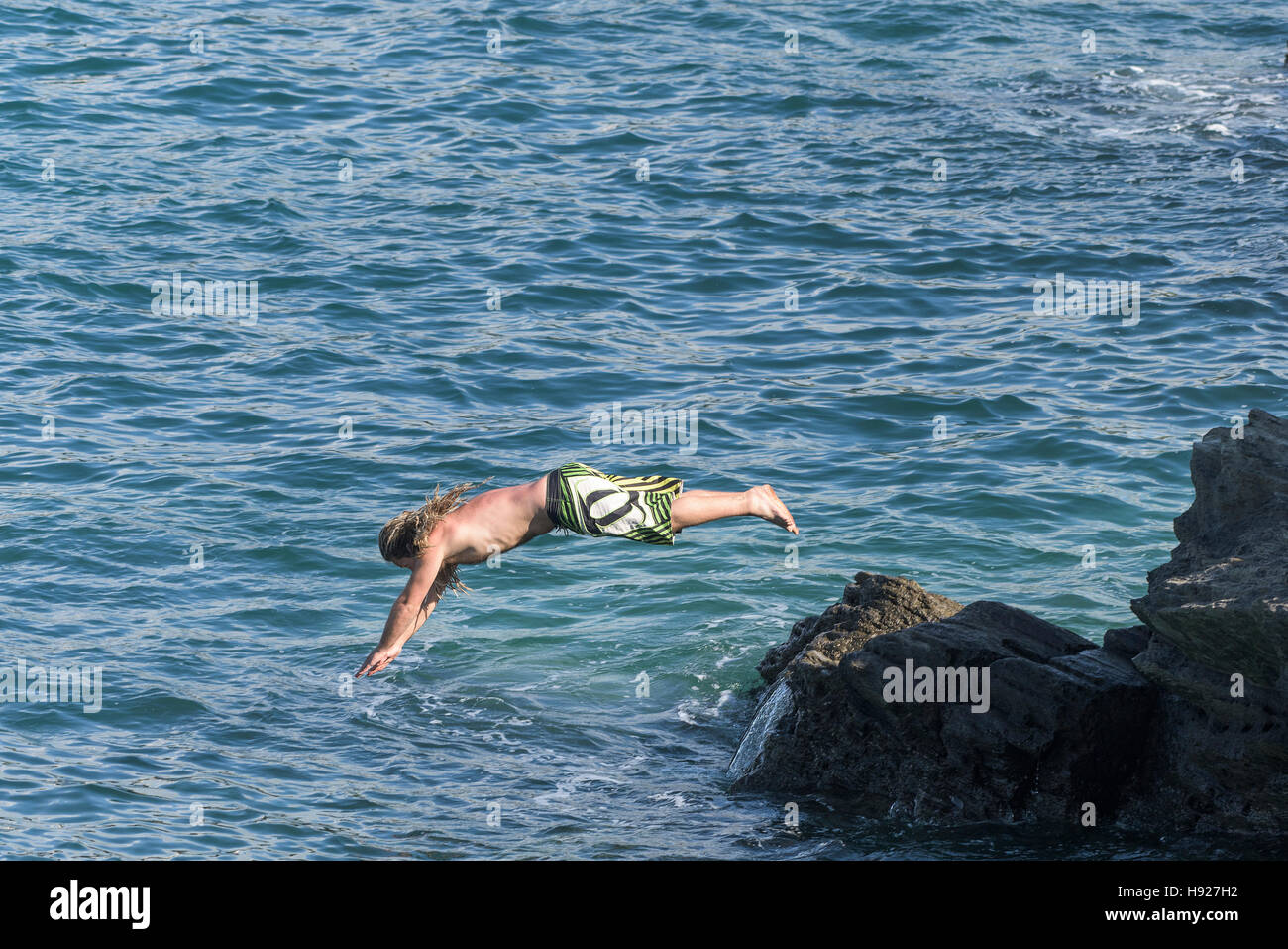 A holidaymaker dives into the sea off rocks on The Headland in Newquay in Cornwall. - Stock Image