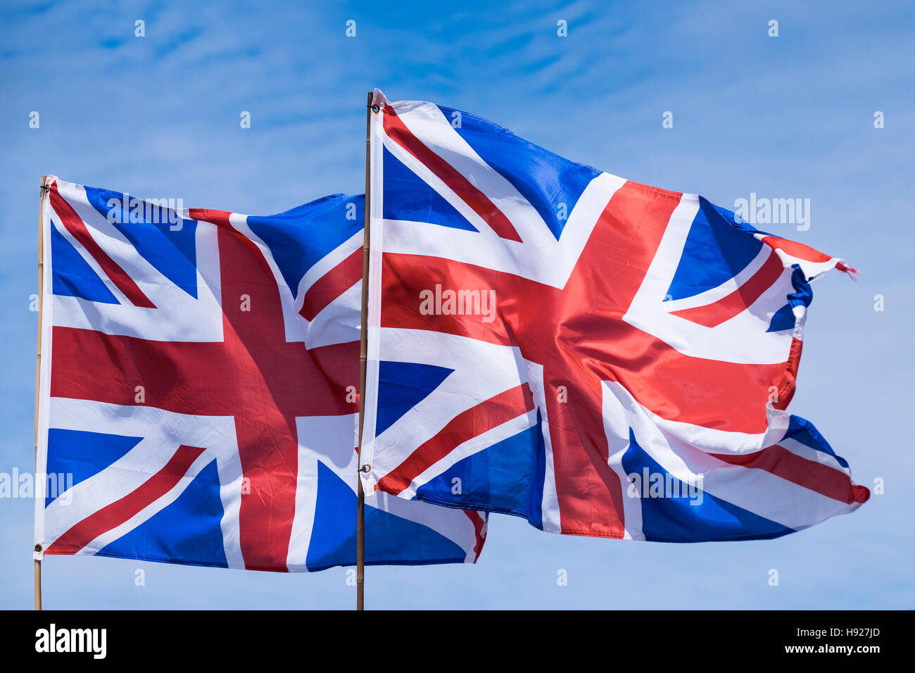 Two Union flags flying against a blue sky. - Stock Image