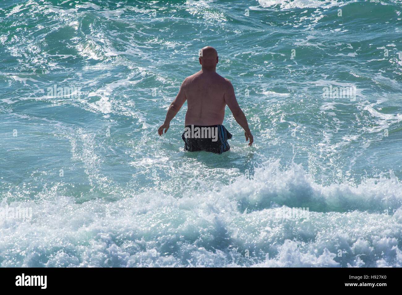 A holidaymaker cooling off in the sea at Fistral Beach in Newquay in Cornwall. - Stock Image