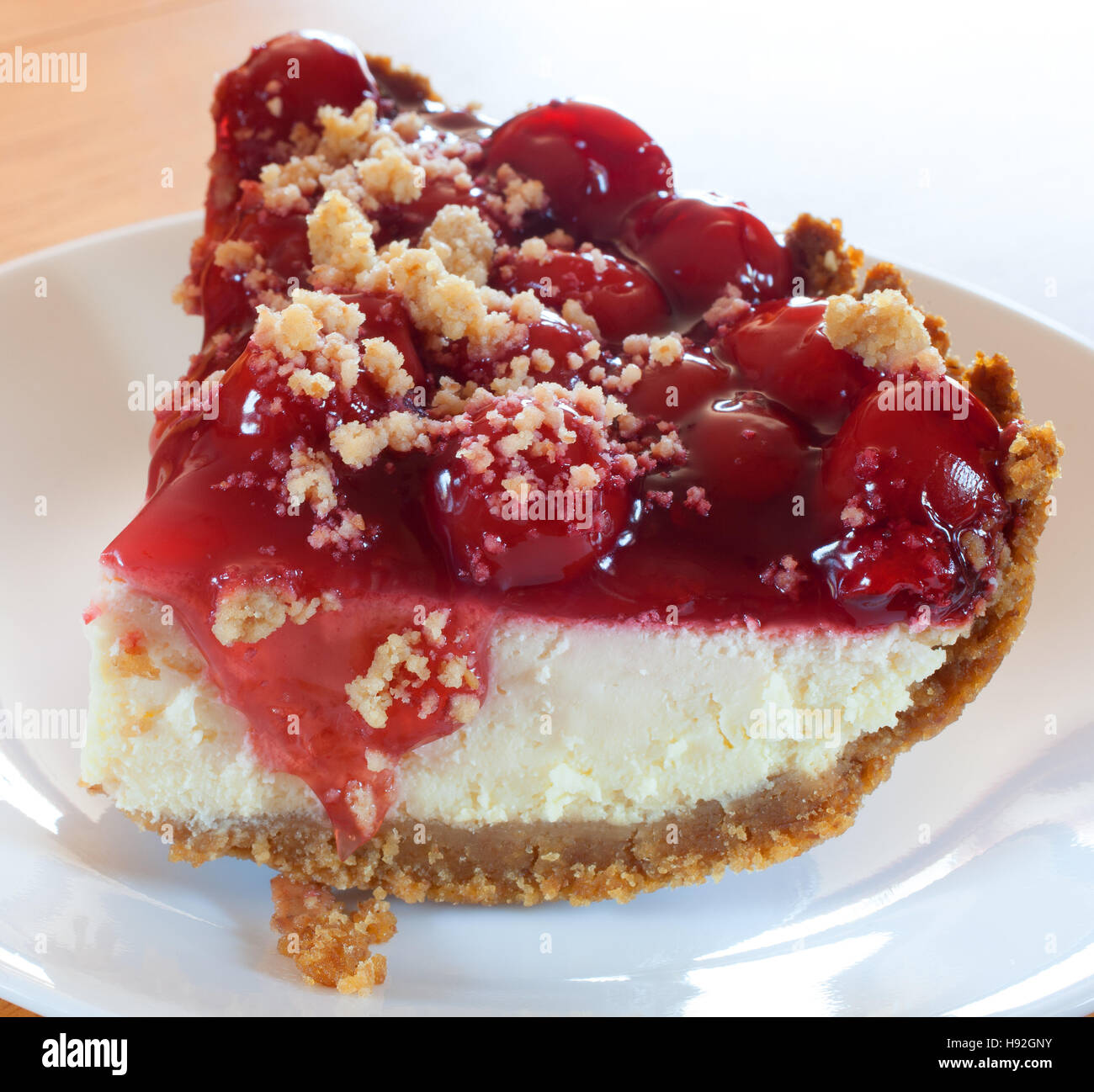 Thick piece of cheesecake with cherries and graham cracker crust - Stock Image