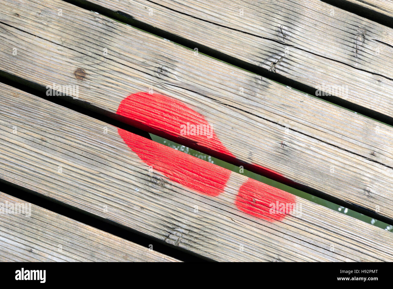 Red painted footprint on Southwold Pier, UK - Stock Image