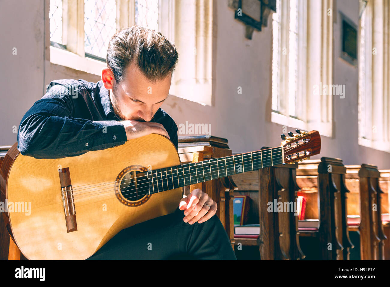 Young male classical musician with a guitar - Stock Image