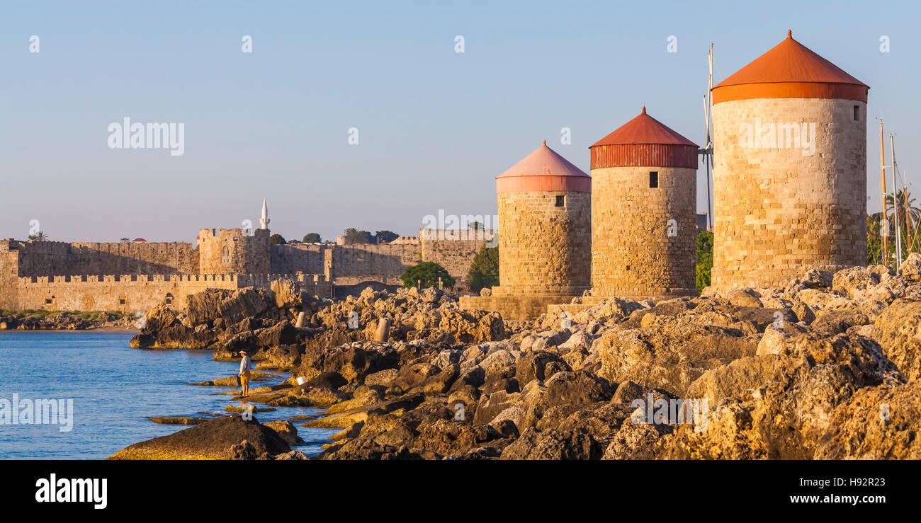 ANGLER, HISTORIC WINDMILLS, MANDRAKI HARBOR, PORT, CITY OF RHODES, RHODES ISLAND, THE AEGEAN, GREECE - Stock Image