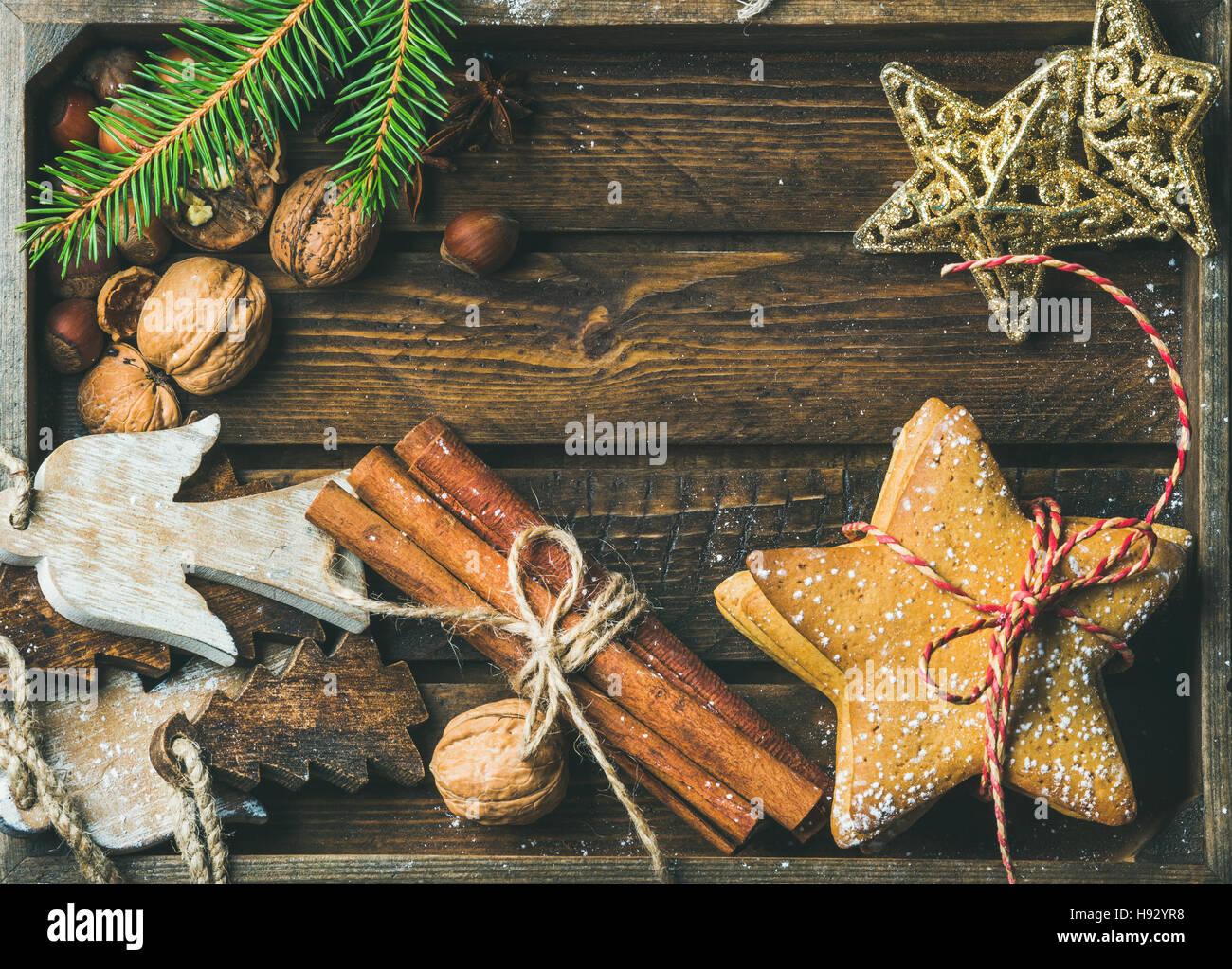 Sweet cookies, wooden angels, decorative golden stars, nuts, cinnamon sticks - Stock Image