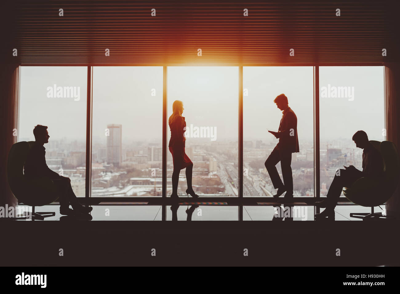 Silhouettes of businessman and businesswoman standing near window of skyscraper and two their male colleagues sitting - Stock Image