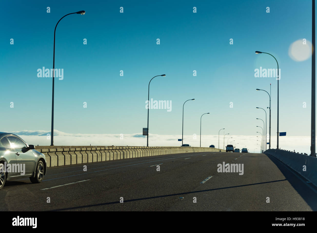 Crossing the Coronado Bridge into a Marine Layer Phenomenon on the ocean, it appears to be driving into the clouds. - Stock Image