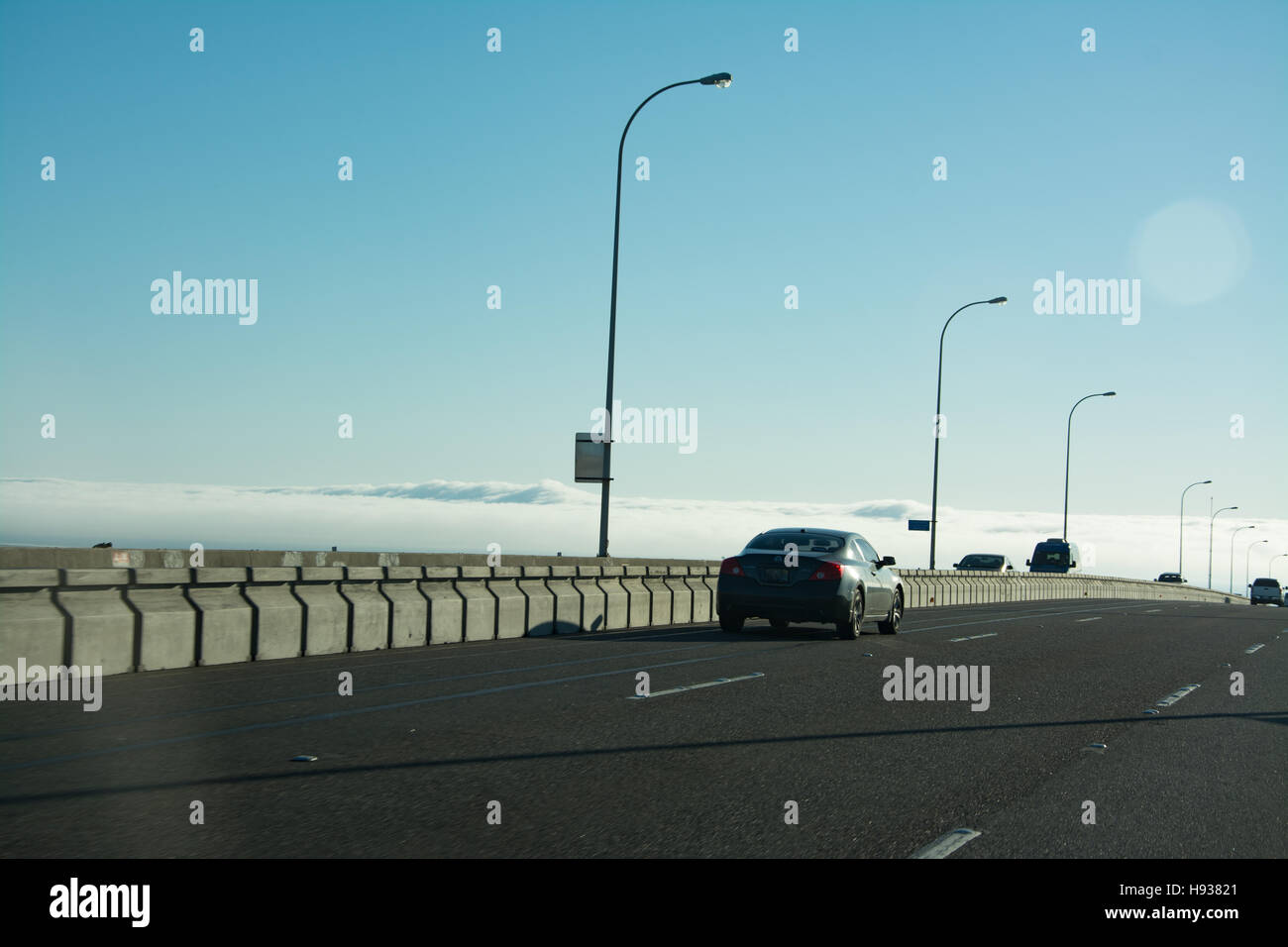 Crossing bridge appears to be above the clouds - Stock Image