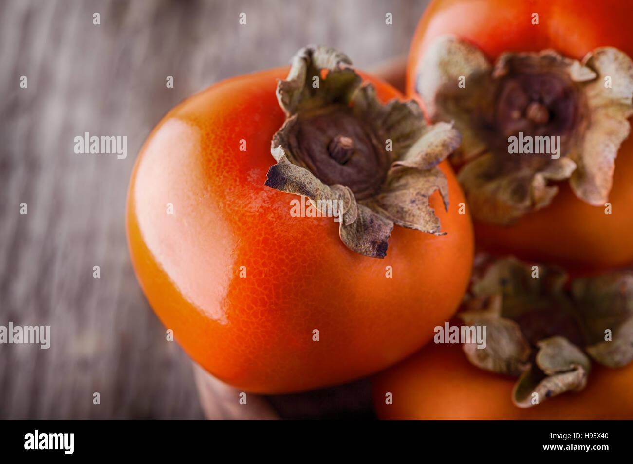 Fresh orange Persimmons on a wooden table. - Stock Image