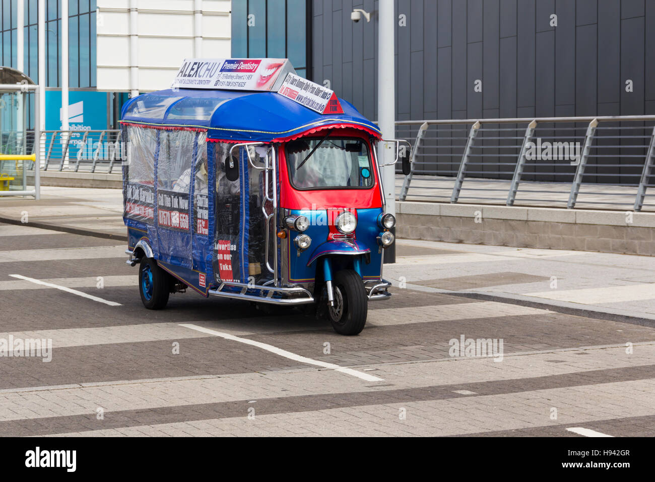 Tuk Tuk three wheel auto rickshaw tourist taxi service travelling along King's Parade on Liverpool's waterfront. - Stock Image