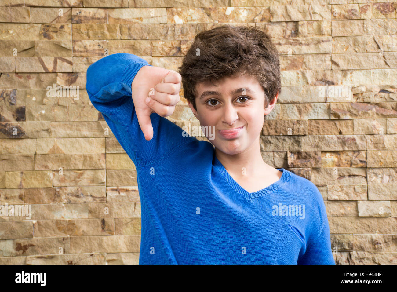 Cheeky boy sticking his tongue out and showing a thumbs down sign - Stock Image