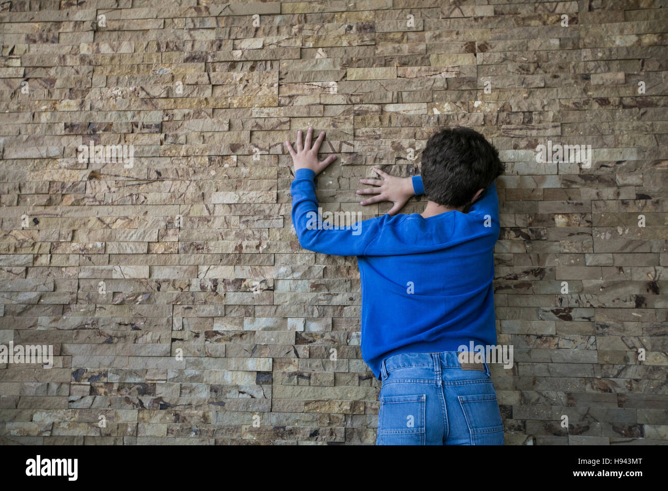 10 years old boy hiding face against the wall - Stock Image