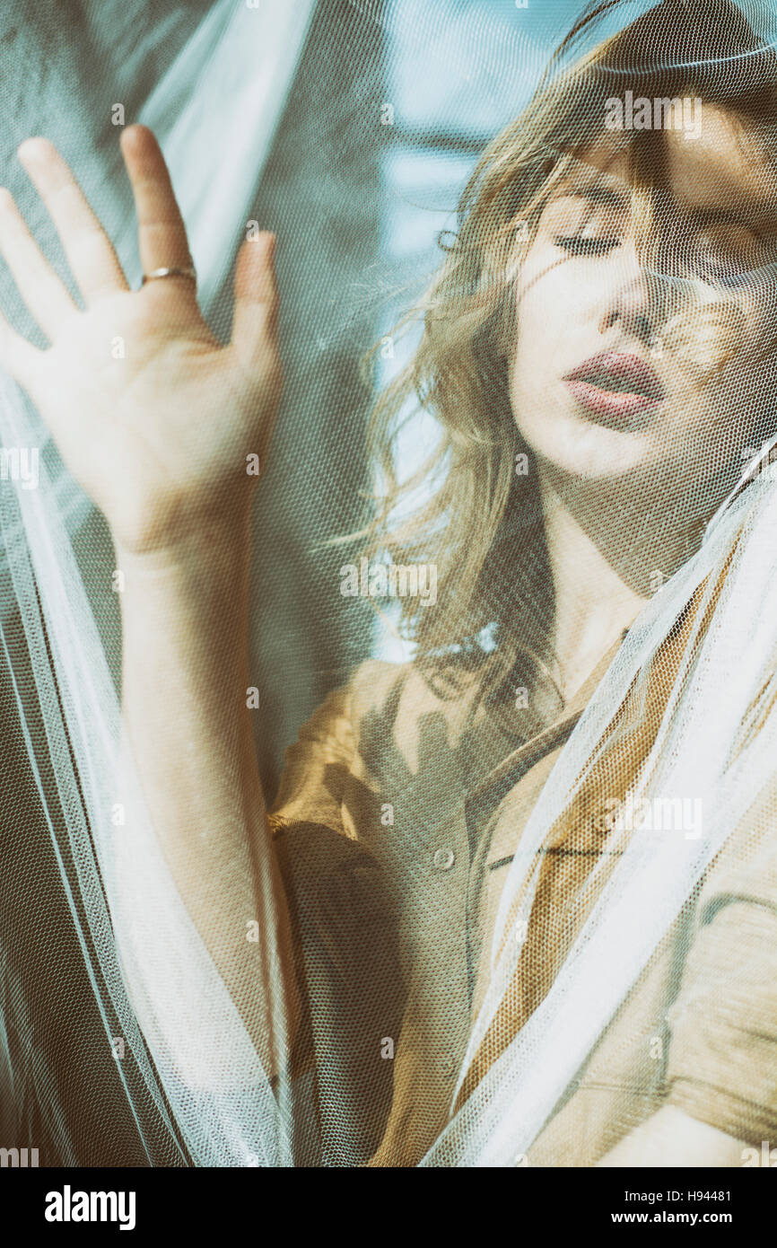 Beautiful young blond woman hand on blinds - Stock Image