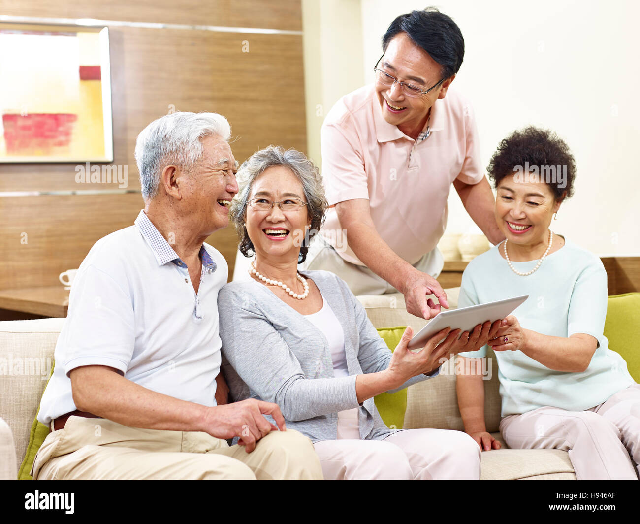 two active senior asian couples looking at tablet computer, happy and laughing - Stock Image
