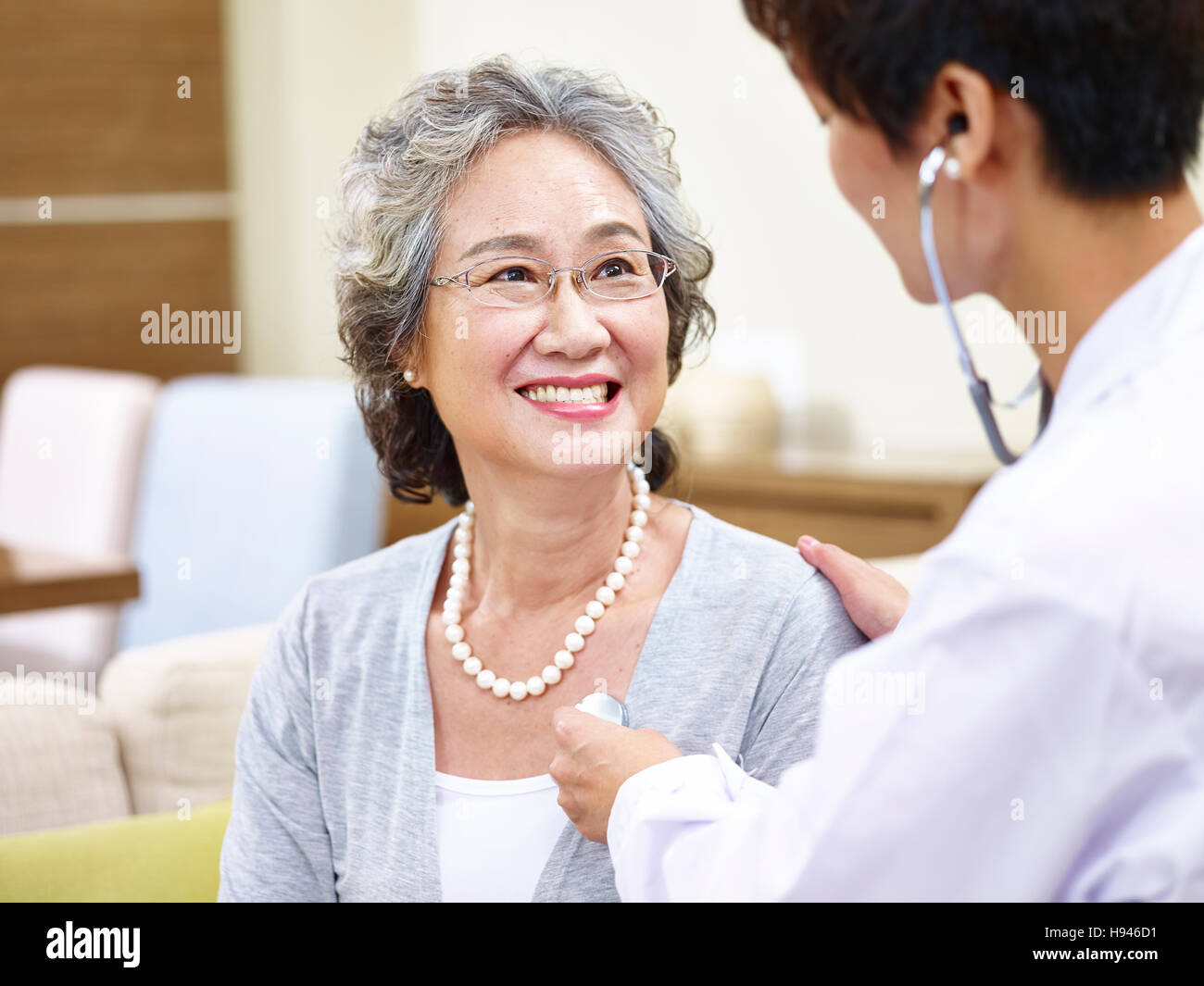 family doctor checking smiling senior asian woman using stethoscope Stock Photo