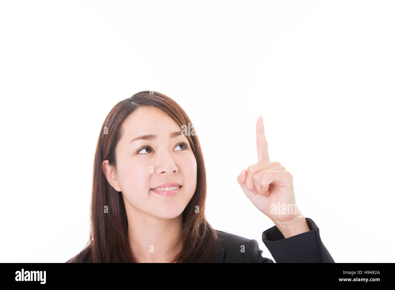 Portrait of young business woman pointing up at white background - Stock Image