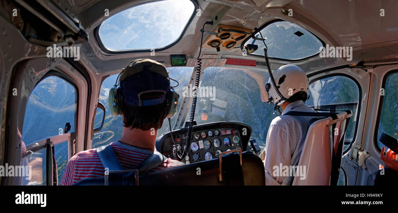 Helicopter cockpit with pilot and passenger in flight to Mount Cook, Aoraki, New Zealand Alps, South Island, New - Stock Image