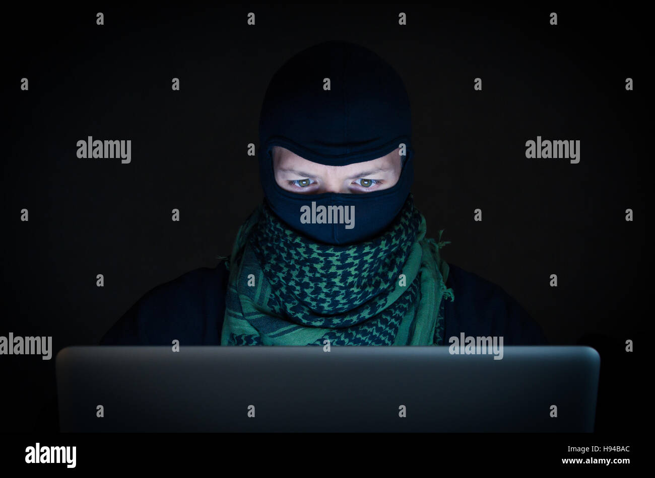 Terrorist working on his computer. Concept about international crisis, war and terrorism - Stock Image