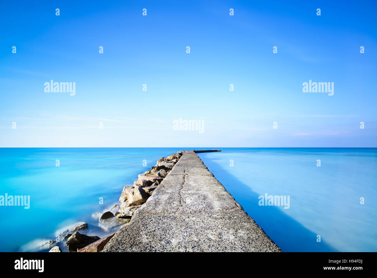 Concrete and rocks pier or jetty on a blue ocean water. Long Exposure photography - Stock Image