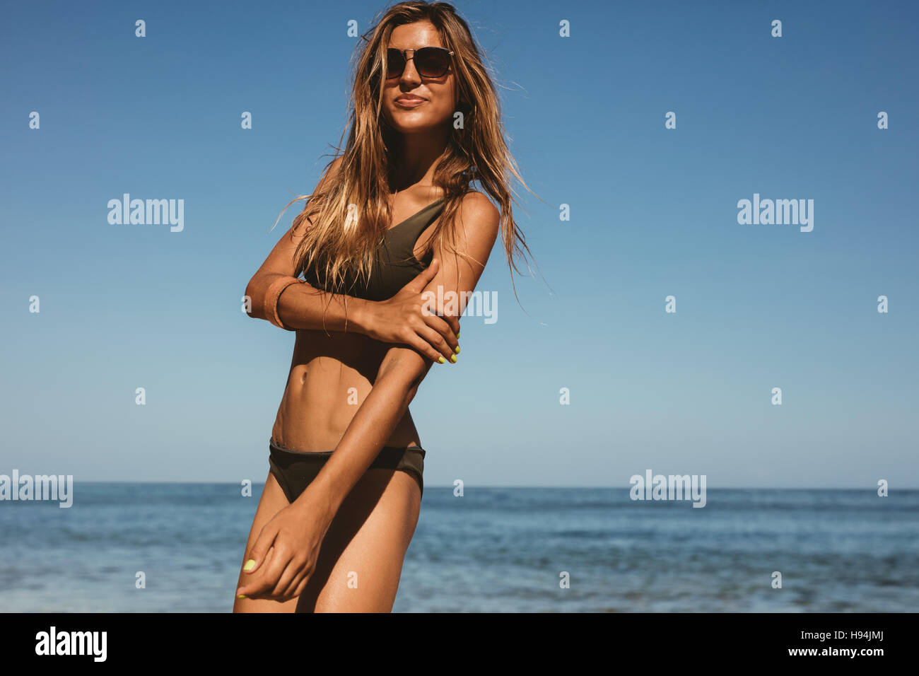 6ba661642b Portrait of young woman in sunglasses and swimsuit on the beach. Female  model posing in bikini on the sea shore on a summer day.