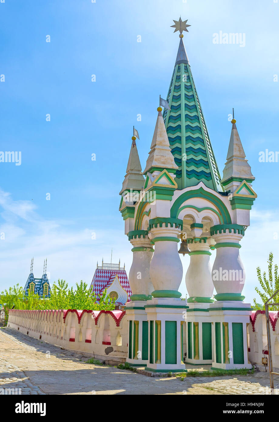 The small green tower, topped with the golden star, has colorful conical roof, figured pillars and located at the - Stock Image