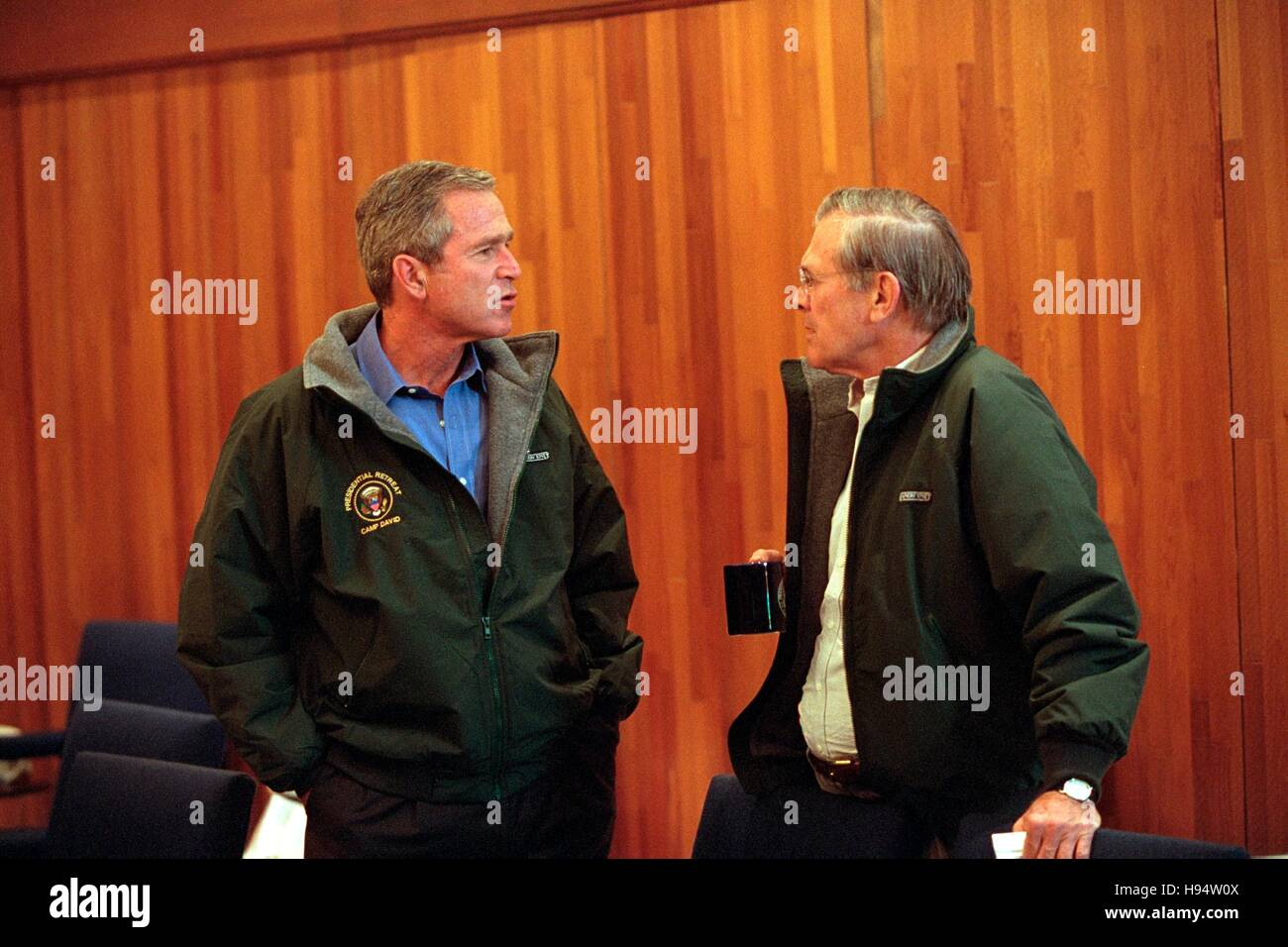 U.S. President George W. Bush talks to Secretary of Defense Donald Rumsfeld during a National Security Council meeting - Stock Image