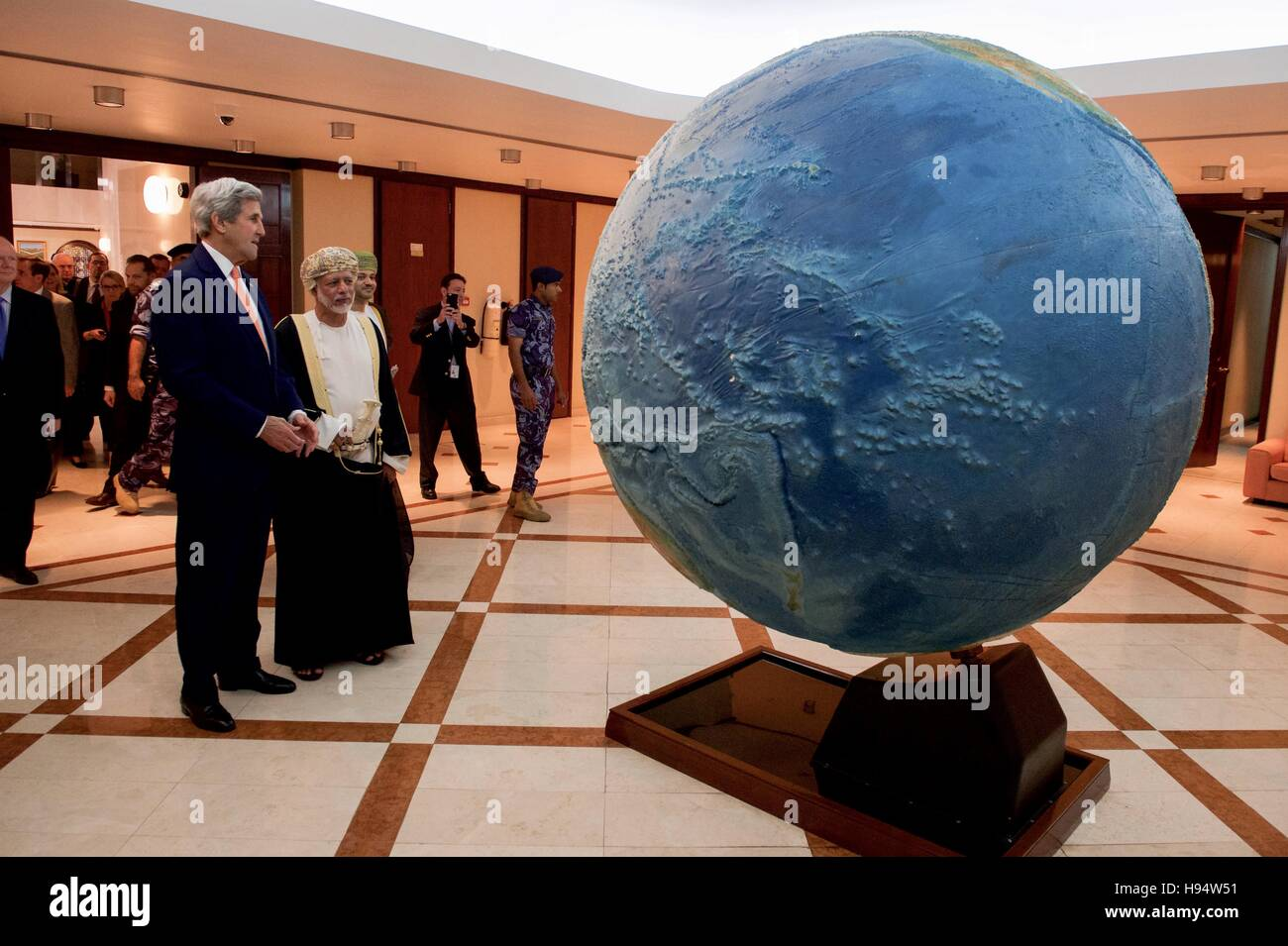 U.S. Secretary of State John Kerry and Omani Foreign Minister Yusuf bin Alawi look at a rotating globe at the Ministry - Stock Image