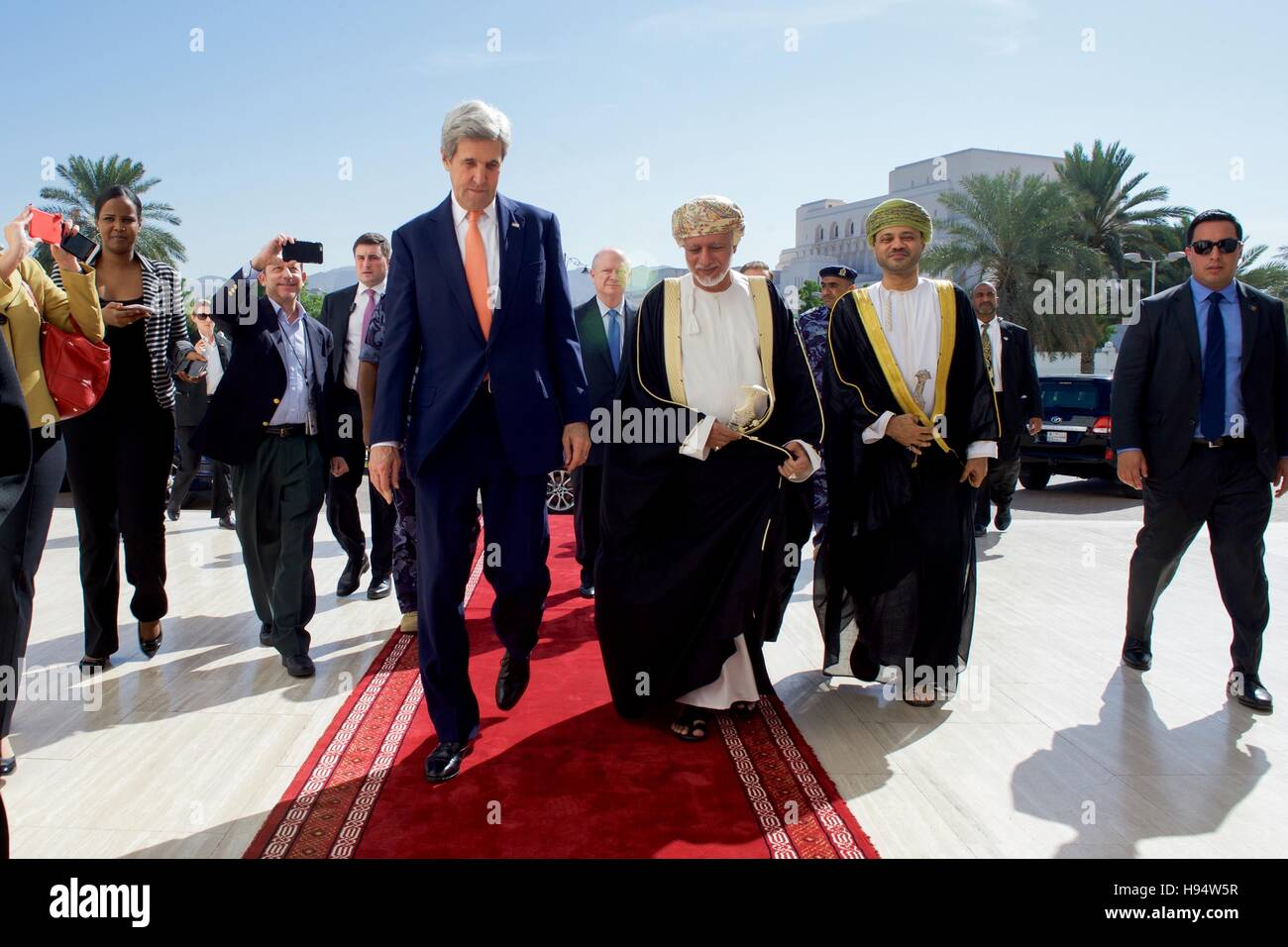 Omani Foreign Minister Yusuf bin Alawi escorts U.S. Secretary of State John Kerry as he arrives at the Ministry - Stock Image