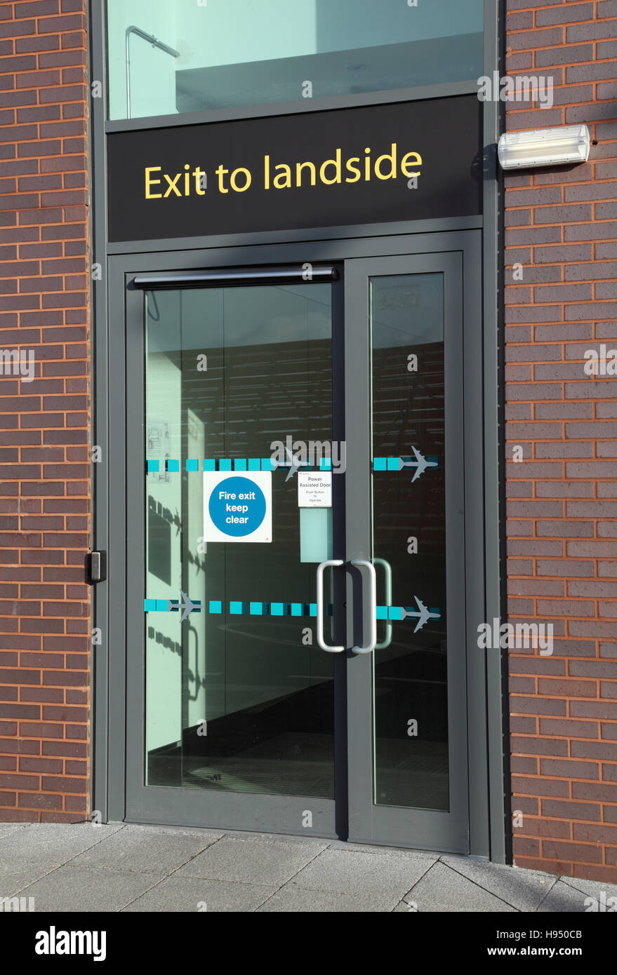 Staff exit from Airside to Landside areas at Gatwick Airport, UK. Large 'Exit to Landside' sign above door. - Stock Image