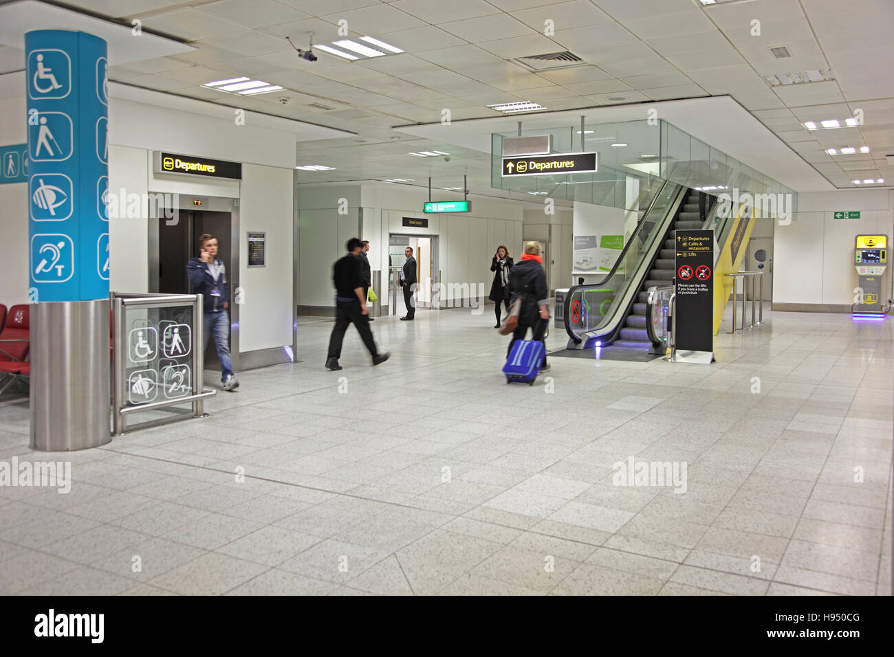 Interior of Gatwick Airport's North Terminal showing lift and escalator signposted 'Departures' with - Stock Image