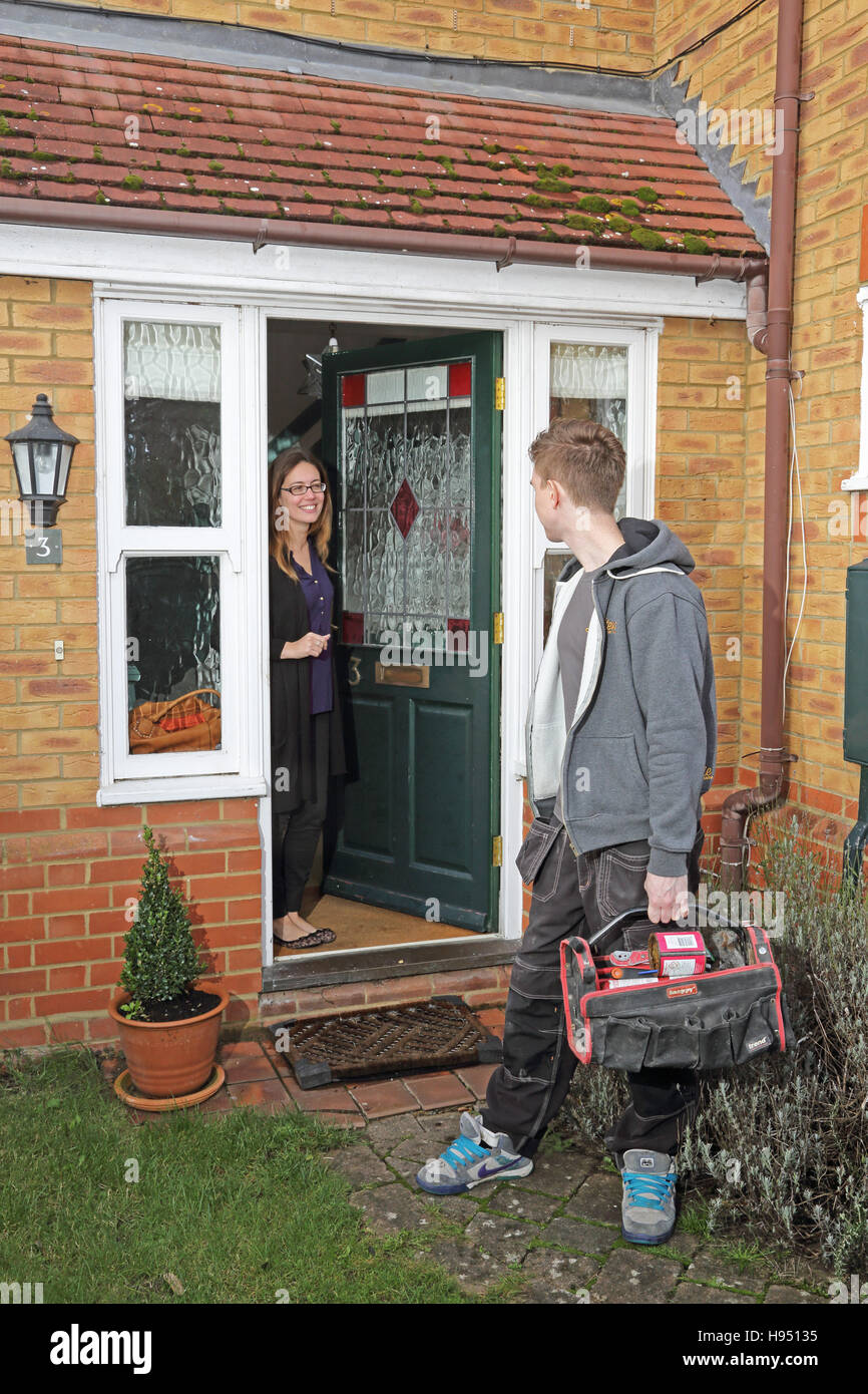 A young plumber/builder and a female householder talk as he leaves a private home after completing a job. Stock Photo