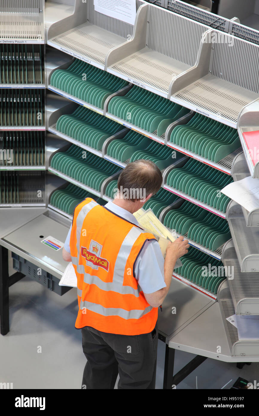 A single postman works at an empty sorting desk in a new Post Office sorting office in Southern England, UK - Stock Image