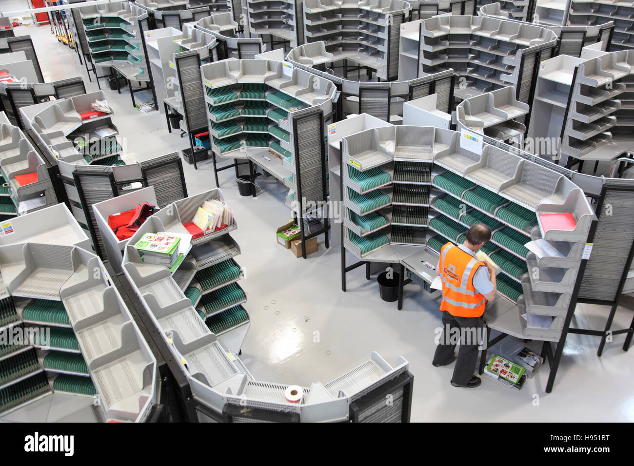 A single postman works at a sorting desk in a new Post Office sorting office in Southern England, UK - Stock Image