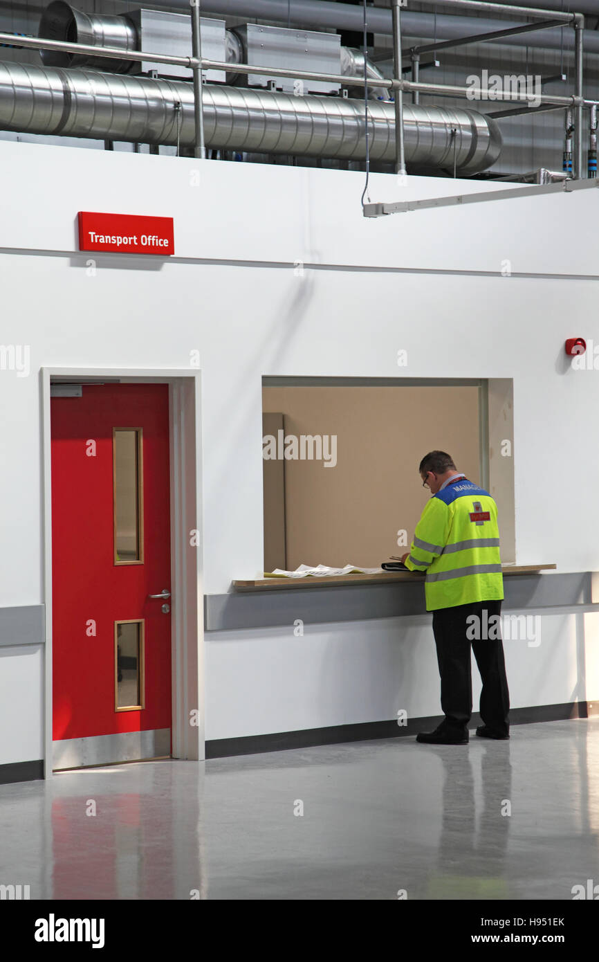 A postman waits at the Transport Office reception in a new Post Office sorting office in Southern England, UK - Stock Image