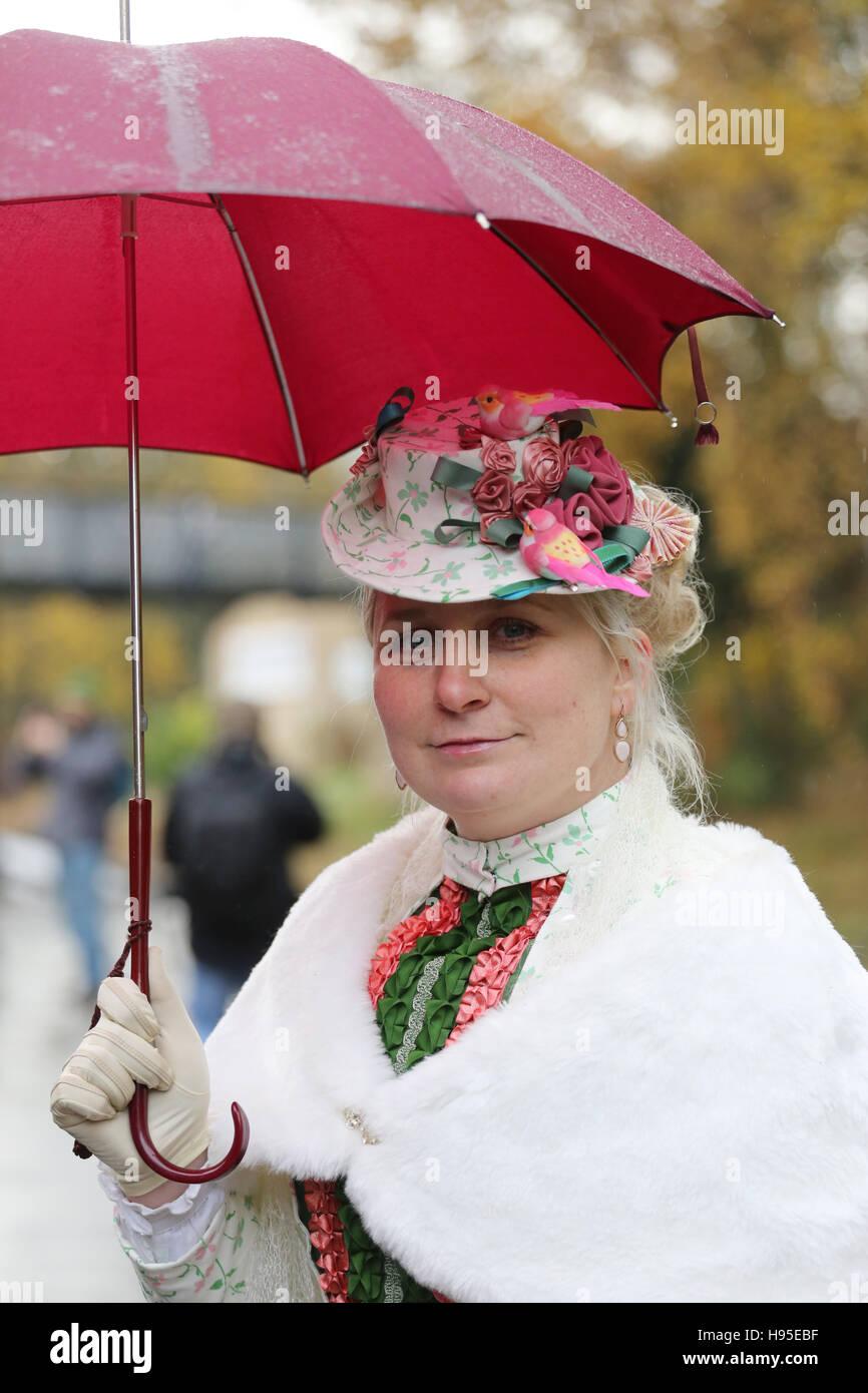 Haworth, UK. 19th Nov, 2016. A women wearing Victorian clothing stood under a red umbrella, Haworth, 19th November Stock Photo
