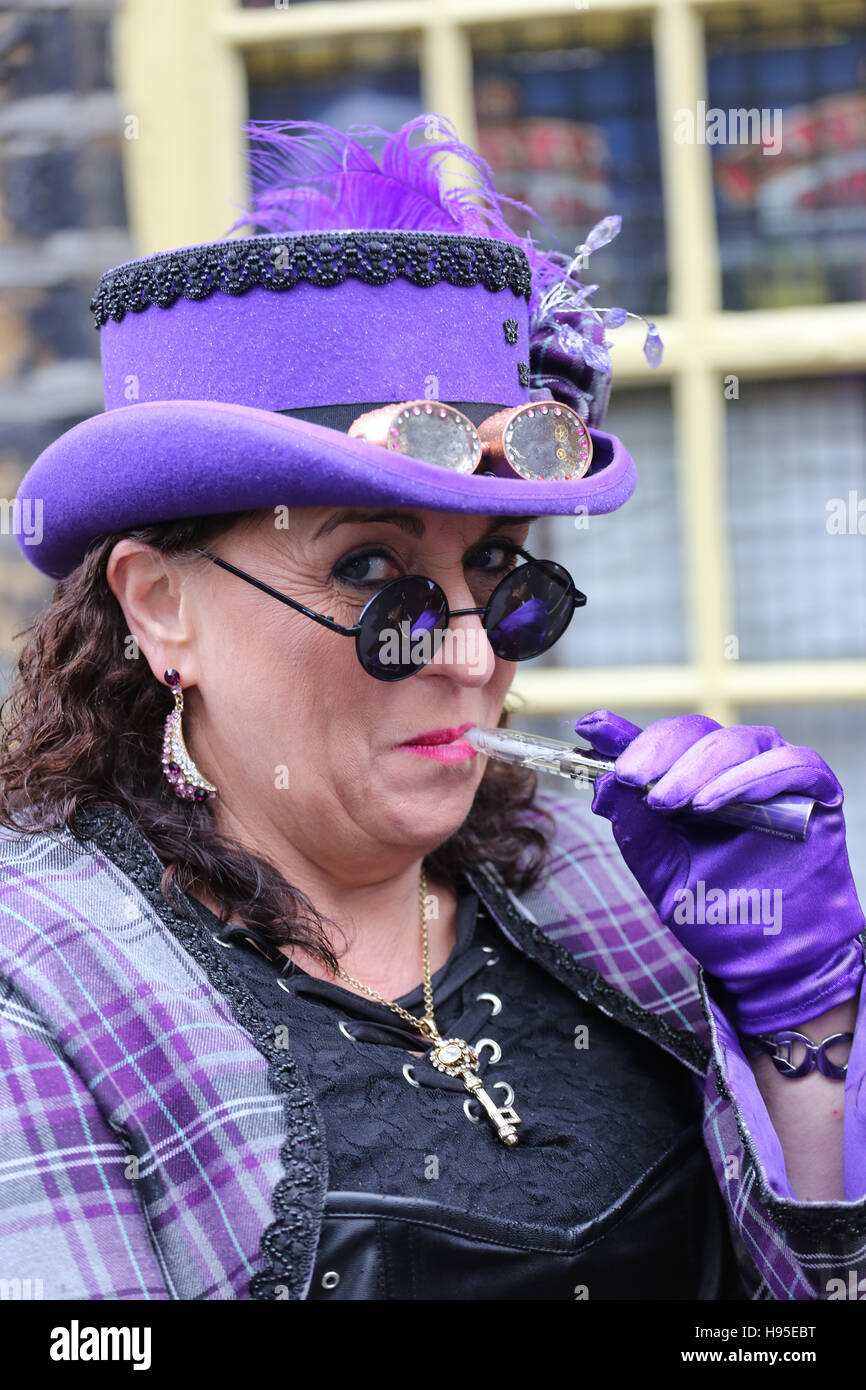 Haworth, UK. 19th Nov, 2016. A women in a purple Steampunk outfit with an electronic cigarette, Haworth, 19th November Stock Photo