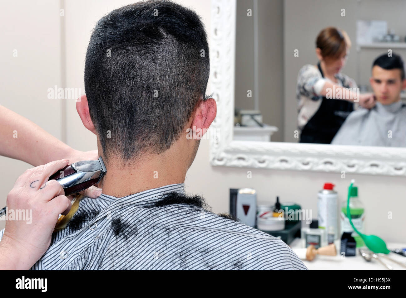 Barber shop that performs the haircut of a young boy with electric clippers. - Stock Image